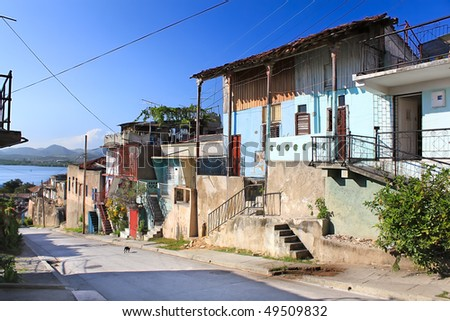 Panoramic view of street with crumbling buildings and view on a bay in Santiago de Cuba , Cuba