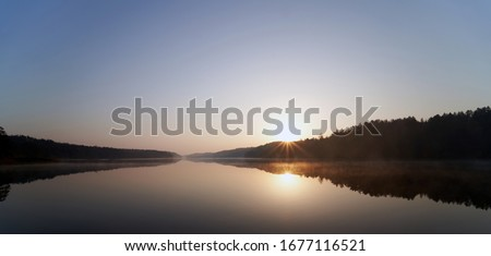 Photo of  Panoramic view of sunrise over the lake Asveja in Asveja Regional Park. Beautiful landscape with fog in morning, Lithuania.