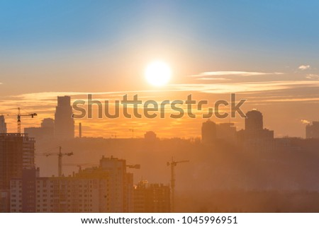 Panoramic view of sunset in the city with silhouette of buildings and industrial cranes