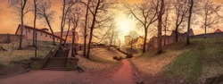 Panoramic view of sunset over medieval stone castle ruins with old stone stairs in the park