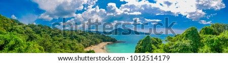 Panoramic view of Thai beach, Phuket, Thailand. Tropical white sandy and tranquil beach with turquoise clear water and palm trees background with blue sky colony of Laem Singh beach nearby Surin beach