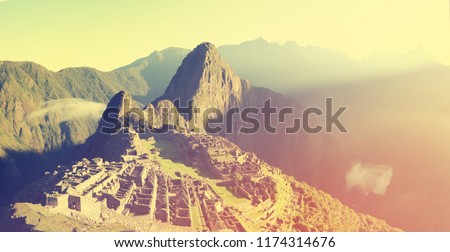 Panoramic view of the ancient Inca City of Machu Picchu, Peru./ The photo is colored and decorated in retro style.