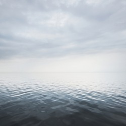Panoramic view of the Baltic sea from a sandy shore. White fog, mist. Dramatic sky, clouds. Seascape. Weather, climate change, nature, danger, shipwreck concepts. Picturesque monochrome scenery