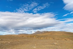 Panoramic view of the barren Icelandic Highlands with volcanos and mountains in the northern part of Iceland with a beautiful blue sky with large white fluffy clouds