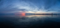 Panoramic View of the Calm Water on the Pacific Ocean Coast during a colorful cloudy sunset. Taken in White Rock, Vancouver, British Columbia, Canada.