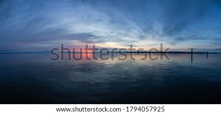 Panoramic View of the Calm Water on the Pacific Ocean Coast during a colorful cloudy sunset. Taken in White Rock, Vancouver, British Columbia, Canada. ストックフォト ©
