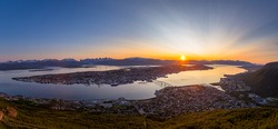 Panoramic view of the city of Tromso, located above the arctic circle in Norway. Various city landmarks are visible, with the midnight sun setting behind the landscape in the background.