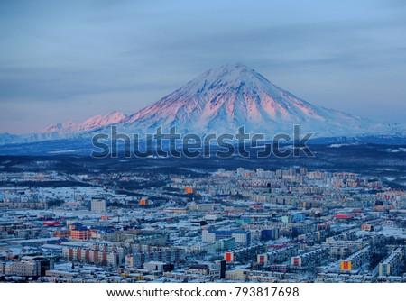Panoramic view of the city Petropavlovsk-Kamchatsky and volcanoes: Koryaksky Volcano, Avacha Volcano, Kozelsky Volcano. Russian Far East, Kamchatka Peninsula.