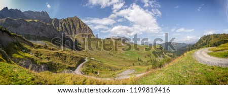 Panoramic view of the Col des Aravis in the French Alps. A dort road is going downhill toward the valley Stok fotoğraf ©