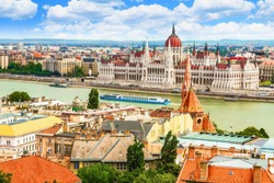 Panoramic view of the Danube river, hungarian parliament building, the Reformed Church and Pest from the opposite side (Buda). Sunny day, green water, cruise boats