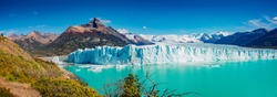 Panoramic view of the gigantic Perito Moreno glacier, its tongue and lagoon in Patagonia in golden Autumn, Argentina, sunny day, blue sky