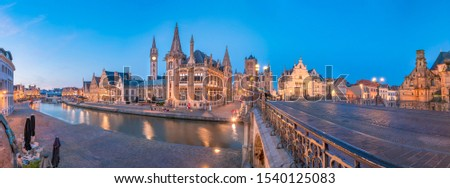 Panoramic view of the Graslei, quay in the promenade next to river Lys in Ghent, Belgium and St Michael's Bridge at dusk. Gent old town is famous for its beautiful illuminated buildings and landmarks  #1540125083