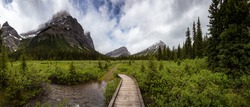 Panoramic View of the Hiking Trail in the Green Meadows with Canadian Rocky Mountains in Background during springtime. Taken near Banff, boarder of British Columbia and Alberta, Canada.