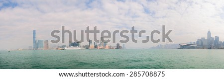 Panoramic view of the Hong Kong skyline from a boat at sea, with the International Commerce Center prominent at the far left of the frame.