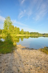 Panoramic view of the lake in a green birch tree forest. Sandy beach. Sunny summer day. Clear blue sky, symmetry reflections on water. Rural scene. Latvia, Europe. Nature, ecology, ecotourism