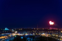 panoramic view of the night city from the high roof, against the dark sky lights up a volley of fireworks in the form of heart, love and celebration, colorful pyrotechnic show at the city festival
