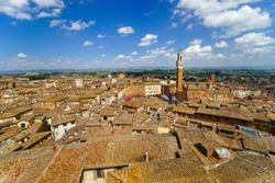 Panoramic view of the old city of Siena, Tuscany, Italy. Piazza del Campo, town hall - Palazzo Pubblico di Siena, Torre del Mangia at noon from Siena Cathedral - Duomo di Siena