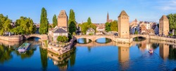 Panoramic view of the Ponts Couverts on the river Ill at the entrance of the Petite France historic quarter in Strasbourg, France, with a tour boat and an electric renting boat cruising on the canals.