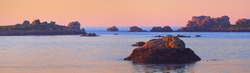 Panoramic view of the rocky shore of Lilia bay at sunset. Plouguerneau, Finistère, Brittany, France. Clear pink sky. Travel destinations, landmarks, recreation, nature. Idyllic landscape