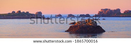 Panoramic view of the rocky shore of Lilia bay at sunset. Plouguerneau, Finistère, Brittany, France. Clear pink sky. Travel destinations, landmarks, recreation, nature. Idyllic landscape Foto stock ©