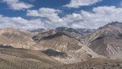Panoramic view of the snow-capped Wakhan mountain range in Afghanistan from the high-altitude desert between Langar and Khargush pass in Gorno-Badakshan, Tajikistan Pamir