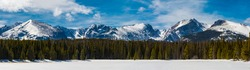Panoramic view of the snow covered Rocky Mountains on a sunny, winter day with a forest and frozen lake view in Rocky Mountain National Park near Estes Park, Colorado