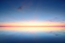 Panoramic view of the snow-covered shore of the frozen Saima lake at sunset. Stunning pink cloudscape. Symmetry reflections on the water. Winter wonderland. Finland