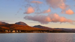 Panoramic view of the valley near the Paps of Jura under the colorful stormy sunset sky. Traditional country houses close-up. Dramatic cloudscape. Craighouse, Jura island, Inner Hebrides, Scotland, UK
