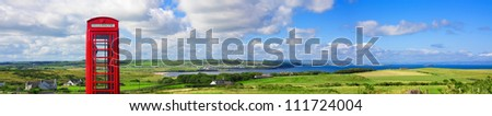 Panoramic view of the village of Portballintrae and the red telephone booth in Antrim, Northern Ireland as seen from the road leading to the Giants Causeway