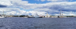 Panoramic view of the warships, frigates and sailboats built in the Neva water area for the Day of the Navy in St. Petersburg, there are many pleasure boats around.