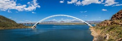 Panoramic view of Theordore Roosevelt Lake Bridge in Arizona's Sonoran Desert in a beautiful sunny day with a blue sky and fluffy white clouds. Desert lake bridge over deep blue water reservoir.