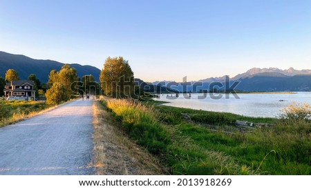 Panoramic view of Traboulay PoCo Trail in Port Coquitlam, BC, Canada. Golden Ears Mountains, Pitt River and greenway. July 2021 Foto stock ©