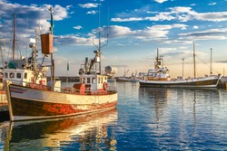 Panoramic view of traditional old wooden fisherman boats lying in harbor in beautiful golden evening light at sunset, town of Husavik, Skjalfandi Bay, Iceland, northern Europe