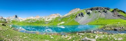 Panoramic view of turquoise Ice lake near Silverton, Colorado on summit rocky mountain peak and snow in August 2019 summer panorama
