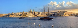 Panoramic view of Valletta waterfront with Carmelite Church dome and St. Pauls Anglican Cathedral at sunset sunlight. Malta