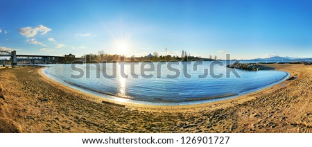 Panoramic view of Vancouver city from the sandy beach side. Sunset above the blue bay