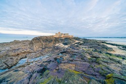 Panoramic view of walled city Saint-Malo in a sunny winter morning and the beach, famous port city of Privateers is known as city corsaire, Brittany, France