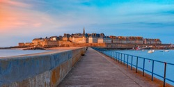 Panoramic view of walled city Saint-Malo with St Vincent Cathedral at sunset. Saint-Maol is famous port city of Privateers is known as city corsaire, Brittany, France