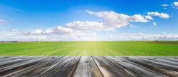 Panoramic view of wooden table top with fresh green field and blue sky in summer. Space for present a product