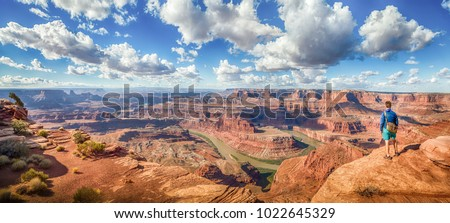 Panoramic view of young hiker standing on a cliff in scenic Dead Horse Point State Park enjoying the view on a beautiful sunny day with blue sky and dramatic clouds in summer, Utah, USA