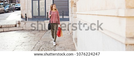 Panoramic view of young woman walking on holiday carrying shopping bags, smiling outdoors. Female consumer visiting stores, travel recreation leisure lifestyle. Stone buildings shopping street.