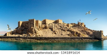 Panoramic view on ancient Fortress of Saladin on the Pharaoh Island in the Gulf of Aqaba and flying seagulls over the Red Sea. Old Castle of Sultan Salah ad-Din in Taba, travel on Sinai Peninsula. Stock fotó ©