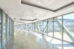 Panoramic view on empty office hall with glass wall windows. made of metal and glass. Modern corridor metal and glass construction. Commercial architecture. Warm toning