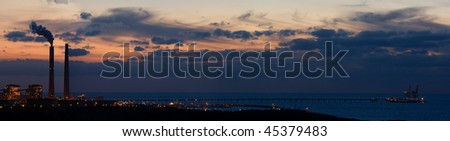 Panoramic view on factory and Mediterranean sea at sunset.