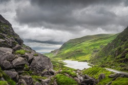 Panoramic view on green mountain hills and a lake in Gap of Dunloe. Dramatic stormy sky in Black Valley, Ring of Kerry, County Kerry, Ireland