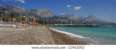 Panoramic view on public beach, Mediterranean Sea and mountains in popular touristic resort Kemer (Antalya), Turkey.