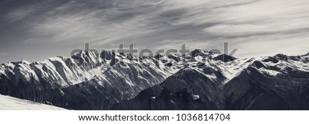 Panoramic view on sunlight snowy mountains in nice morning. Caucasus Mountains. Svaneti region of Georgia. Black and white toned landscape.