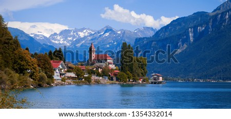 Panoramic view on the Brienz town on lake Brienz by Interlaken, Switzerland. Old fishing town with beautiful church and snow covered blue Alps mountains on background. Switzerland, Bohemia, Europe. #1354332014