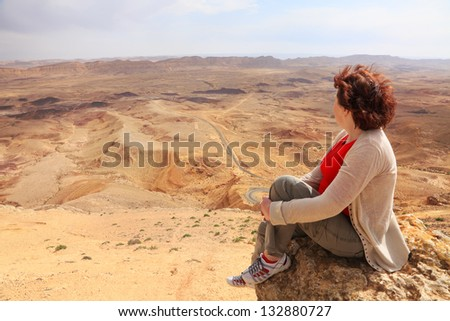 Panoramic view on the color desert and woman watching down from cliff. Negev desert. South of Israel