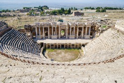 Panoramic view onto antique theater of ancient city Hierapolis, Pamukkale, Turkey. Scene decorated with classic statues, basreliefs, columns & portico. It's included in UNESCO List as all city objects